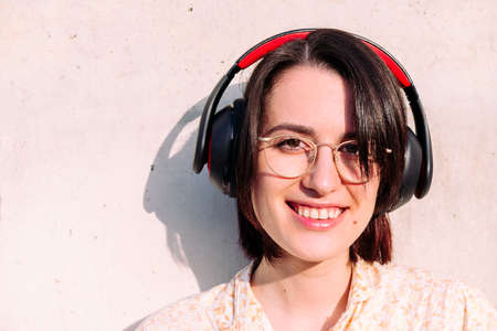 portrait of a happy young woman with headphones and glasses smiling looking to camera, concept of technology, youth and urban lifestyle, copy space for text