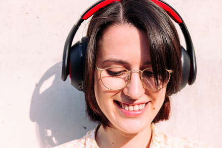 portrait of a beautiful teenage girl with headphones and glasses smiling, concept of technology, youth and urban lifestyle, copy space for text