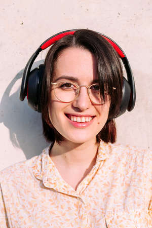vertical portrait of a happy young woman with headphones and glasses smiling looking to camera, concept of technology, youth and urban lifestyle