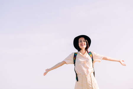 young woman with hat smiling free and happy with open arms in front of clean sky, travel and tourism concept, text copy space