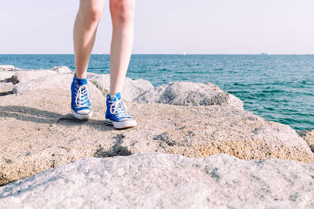 front view of the legs of a young girl in sneakers walking on the rocks by the sea, copy space for text