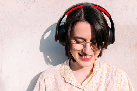 portrait of a beautiful young woman with headphones and glasses smiling, concept of technology, youth and urban lifestyle, copy space for text Archivio Fotografico