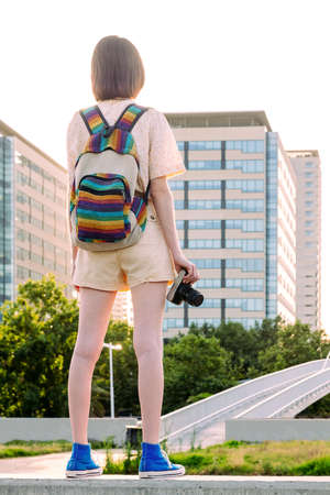 rear view of a young traveler woman with backpack and camera standing in front of the city, concept of youth and digital nomad lifestyle, vertical photo
