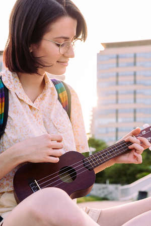 vertical portrait of a beautiful young woman playing ukulele at sunset in the city, amateur music concept and artistic lifestyle, copy space for text Archivio Fotografico
