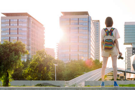 rear view of a young traveler woman with backpack and camera standing in front of the city, concept of youth and digital nomad lifestyle, copy space for text