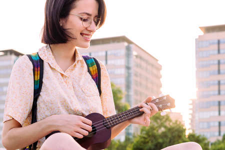 portrait of a smiling young woman playing ukulele at sunset in the city, amateur music concept and artistic lifestyle, copy space for text Archivio Fotografico