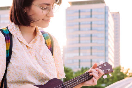 portrait of a beautiful young woman playing ukulele at sunset in the city, amateur music concept and artistic lifestyle, copy space for text Archivio Fotografico