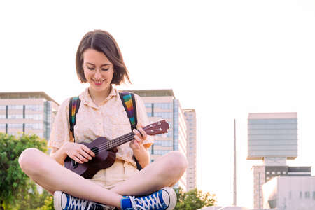 beautiful young woman in sneakers playing ukulele at sunset in the city, amateur music concept and artistic lifestyle, copy space for text Archivio Fotografico