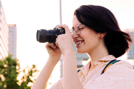beautiful traveler woman smiling and taking a photo with a vintage camera, concept of youth and creative lifestyle, copy space for text