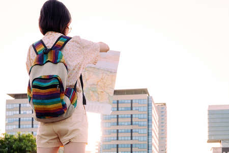 rear view of a young traveler woman with backpack looking a map in front of the city, concept of youth and nomad lifestyle, copy space for text Archivio Fotografico