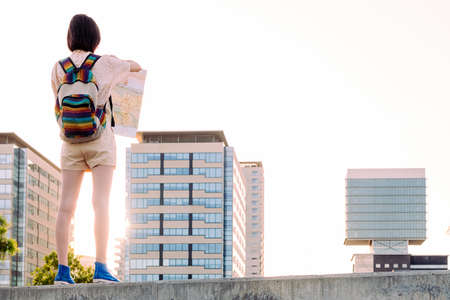 rear view of a young traveler girl with backpack looking a map in front of the city, concept of youth and nomad lifestyle, copy space for text