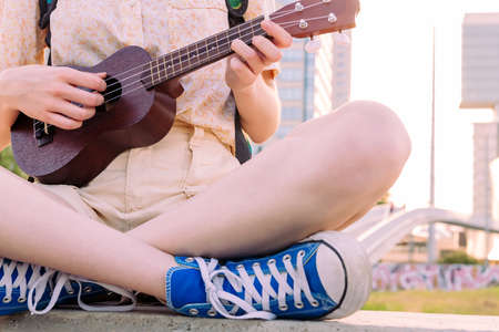 close-up of the hands of an unrecognizable young woman in sneakers playing the ukulele at sunset in the city, concept of amateur music and artistic lifestyle