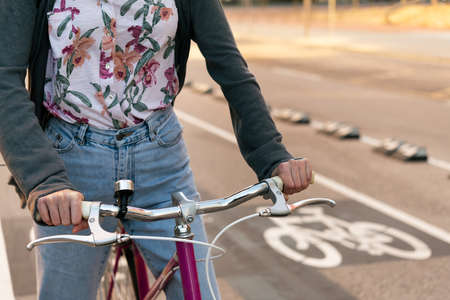 detail of the hands of an unrecognizable young woman at the city riding a retro bicycle by the bike path, concept of active lifestyle and sustainable mobility Archivio Fotografico