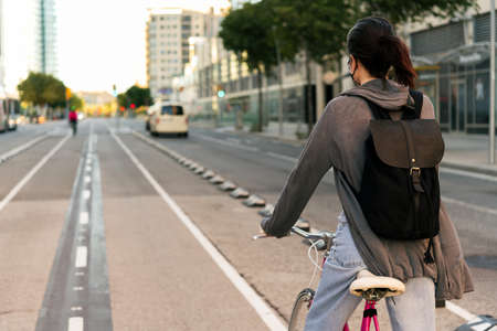 rear view young girl with backpack at the city riding a pink retro bicycle by the bike path, concept of active lifestyle and sustainable mobility Standard-Bild
