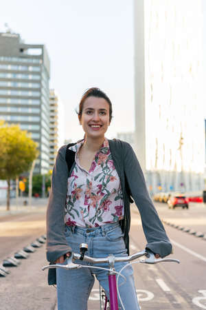 vertical portrait of a smiling young woman at the city riding a pink retro bicycle by the bike path, concept of active lifestyle and sustainable mobility Archivio Fotografico