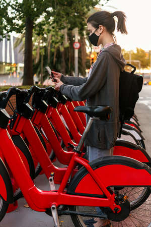 vertical photo of a young girl with protective mask scanning the code with a smart phone to unlock a bike from the urban bike rental parking, concept of active lifestyle and sustainable mobility