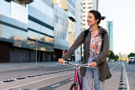 happy young girl smiling and walking with a pink retro bicycle by the bike path at city, concept of active lifestyle and sustainable mobility