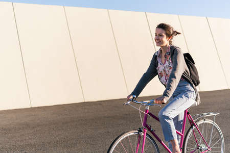 smiling young girl riding a pink retro bike, concept of active lifestyle and sustainable urban mobility