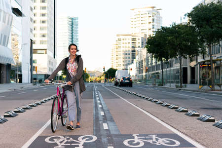 smiling young woman walking with a pink retro bicycle by the bike path at city, concept of active lifestyle and sustainable mobility Archivio Fotografico