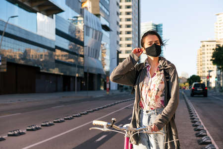 young woman with a retro bike at city adjusting her protective mask, concept of active lifestyle, protection against covid and sustainable mobility Archivio Fotografico