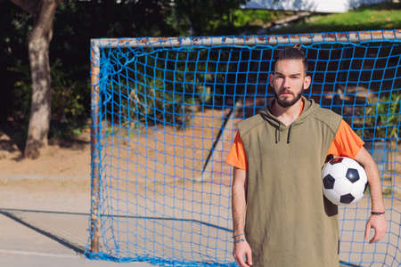 handsome hipster soccer player in front of the goal of an urban court with the ball under his arm, concept of healthy lifestyle and urban sport in the city, copy space for text