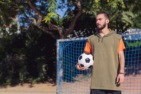 handsome hipster football player in front of the goal of an urban court with the ball under his arm, concept of healthy lifestyle and urban sport in the city, copy space for text