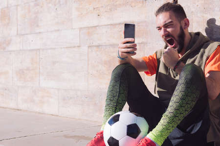 handsome football fan celebrates a victory when he is consulting his smart phone, concept of technology and urban sport lifestyle in the city, copy space for text