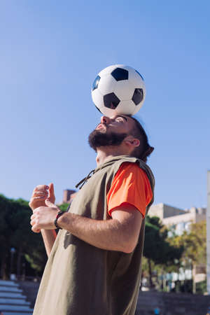 vertical portrait of a soccer player playing balancing the ball on his head, concept of healthy lifestyle and urban sport in the city, copy space for text
