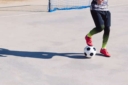 unrecognizable football player stepping on the ball in a concrete football court, concept of healthy lifestyle and urban sport in the city, copy space for text