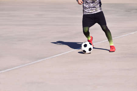 legs of an unrecognizable sportsman playing with the ball in a concrete football court, concept of healthy lifestyle and urban sport in the city, copy space for text
