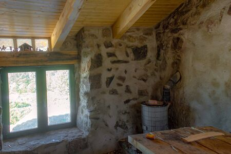 rustic and sober refuge for mountaineers who want to spend the night near the peñalara peak, it is built in stone with an air of old construction, pine wood ceiling that gives it a warm touch, a wood stove and a small window with a beautiful landscape 免版税图像