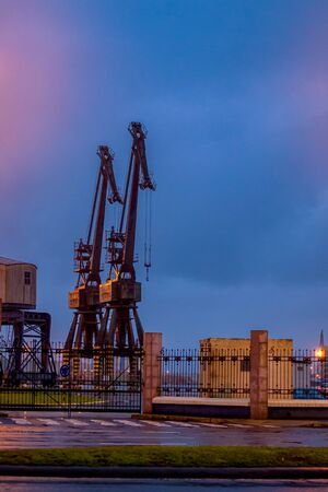 port of coruña, standing at night its two old cranes you rest with your arm raised waiting for the next day's activity to start