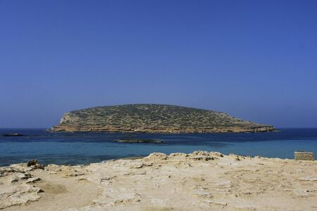 Deserted beach with turquoise waters, bright day, Mountains in the background and bright blue day, with a large rock in the middle