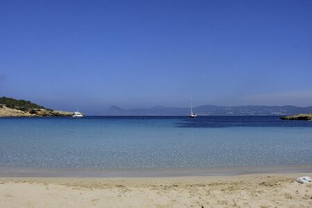 Deserted beach with turquoise waters, bright day, Mountains in the background and bright blue day, two boats sailing
