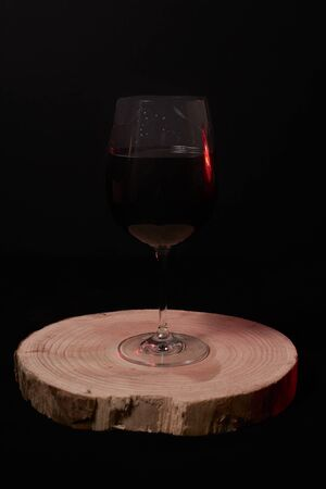 Glass of red wine on wooden stump, on black background, Dark and black