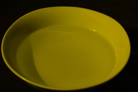 White bowl full of water on black background, calm water, deep yellow color