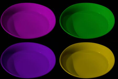Four bowls with water of different colors, magenta, yellow, purple and green, black background, complementary colors