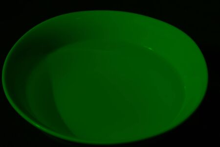 White bowl full of water on black background, calm water, emerald color