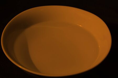 White bowl full of water on black background, calm water, orange color