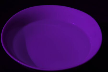 White bowl full of water on black background, calm water, violet color