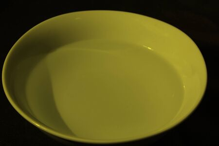 White bowl full of water on black background, calm water, yellow color 版權商用圖片