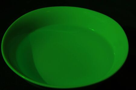 White bowl full of water on black background, calm water, green color
