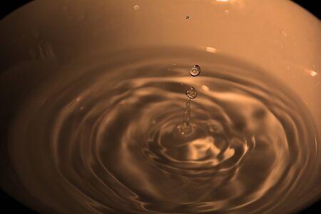 Drop of water on white bowl, orange, black background Reklamní fotografie