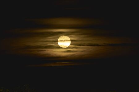 Full moon among yellow clouds, darkness, contrast, fear