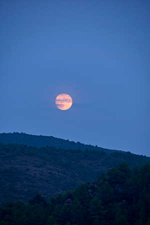 The moon rising between the mountains, full moon, blue tones, mountain, alpine landscape