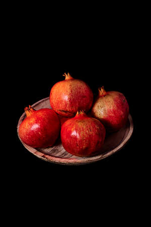 Pomegranates on wooden plate, Black background, macro photography 版權商用圖片