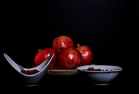 Pomegranates in wooden plate and seeds in bowl with yogurt, Black background, macro photography