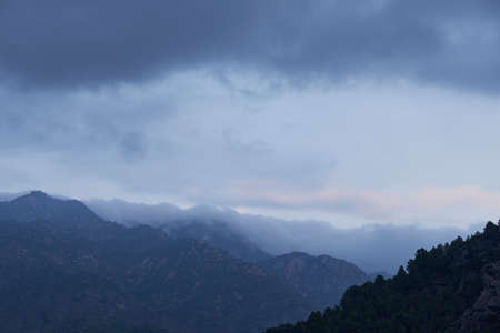 High mountains surrounded by clouds and forests, blue, storm, cold