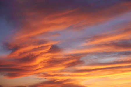 Sunset. Heaven, orange sky. Sun rays. Wallpaper. Clouds. 版權商用圖片