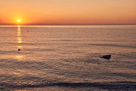 Sunrise on the beach, sun on a rock, lines, oranges